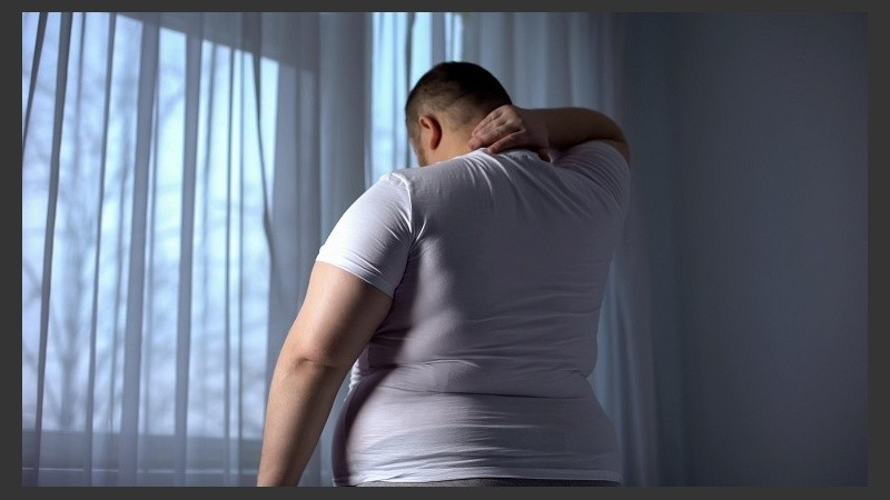 Obese man stretching neck muscles, back pain problems caused by overweight
